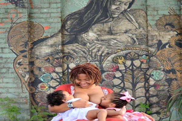Mother breastfeeding in front of a mural.