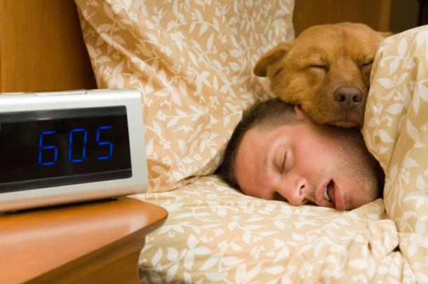 Man sleeping in with dog