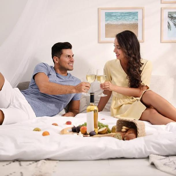 couple toasting with wine in bed