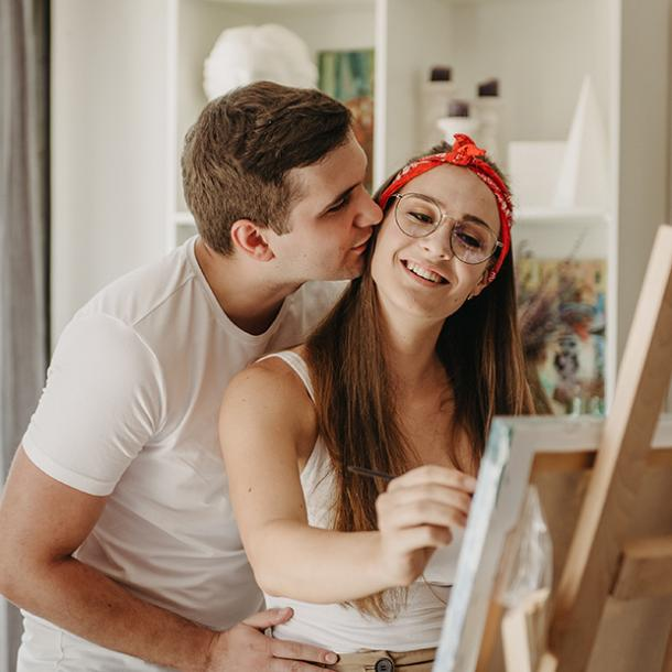 woman painting with man kissing her cheek
