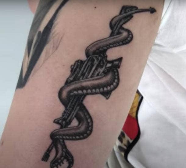 post malone snake coiled around rifle tattoo