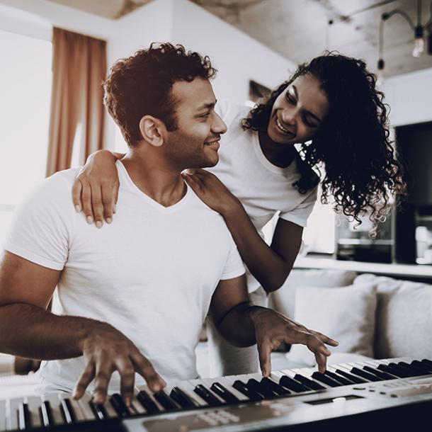 man playing piano with woman standing behind him