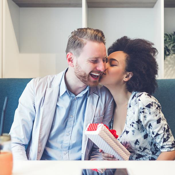 couple kissing woman holding gift