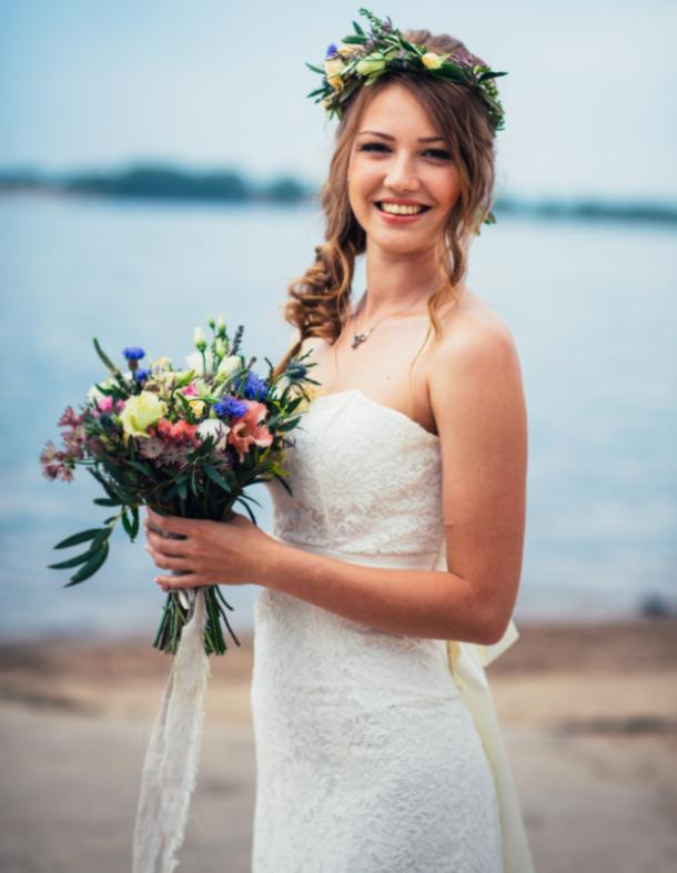 bride on her wedding day holding flowers by the water