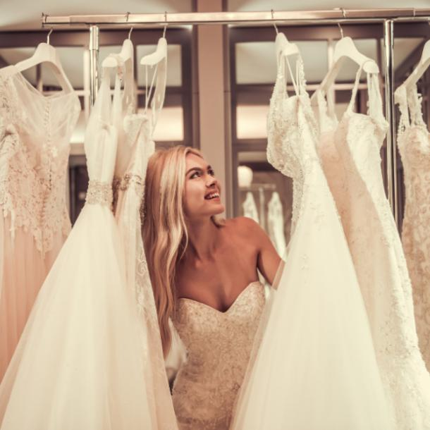bride looking at wedding dresses on a rack