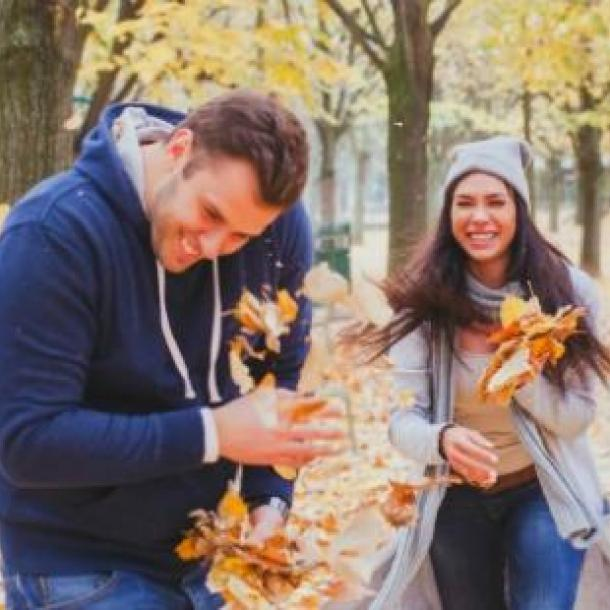 couple playing with fall leaves during cuffing season