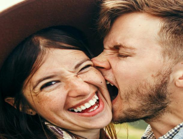 men playfully biting woman's cheek and ears