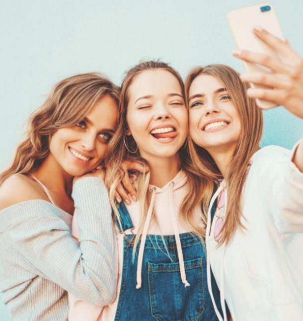 three friends taking selfies together