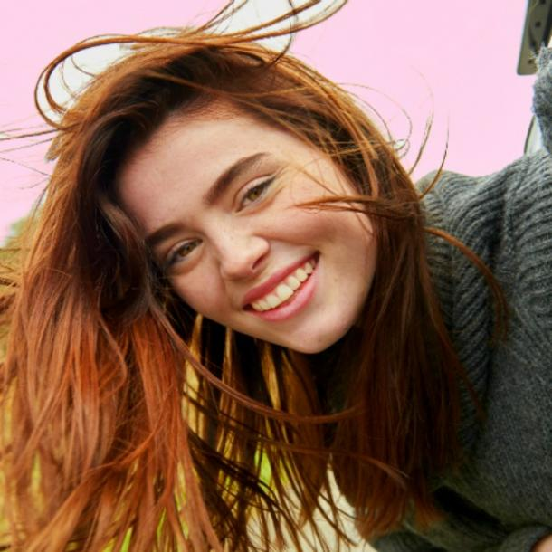 young woman with auburn hair smiles into the camera in a hopeful, romantic way