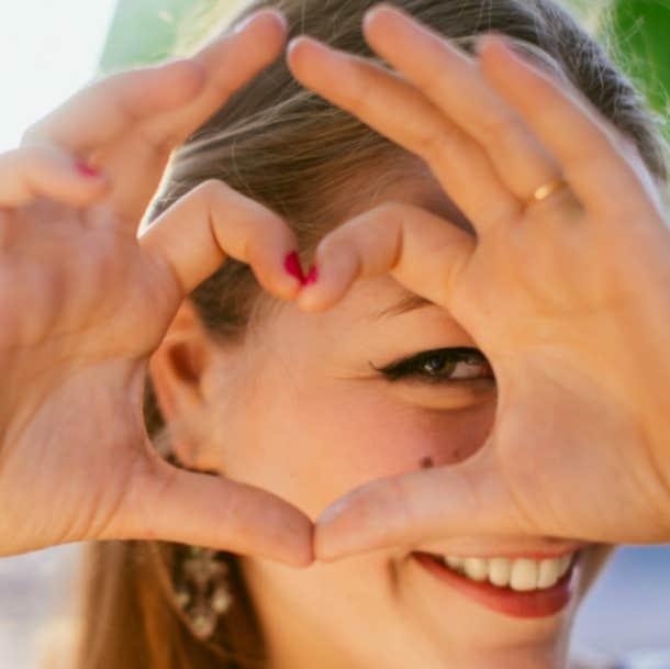 hopeless romantic woman making heart hands