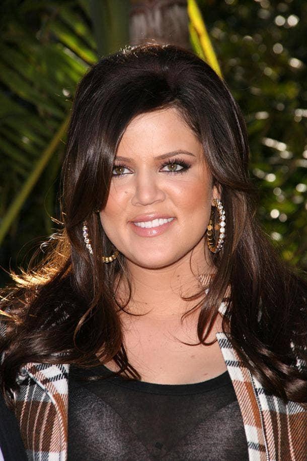 khloe kardashian smiling plaid jacket with earrings and hair bump
