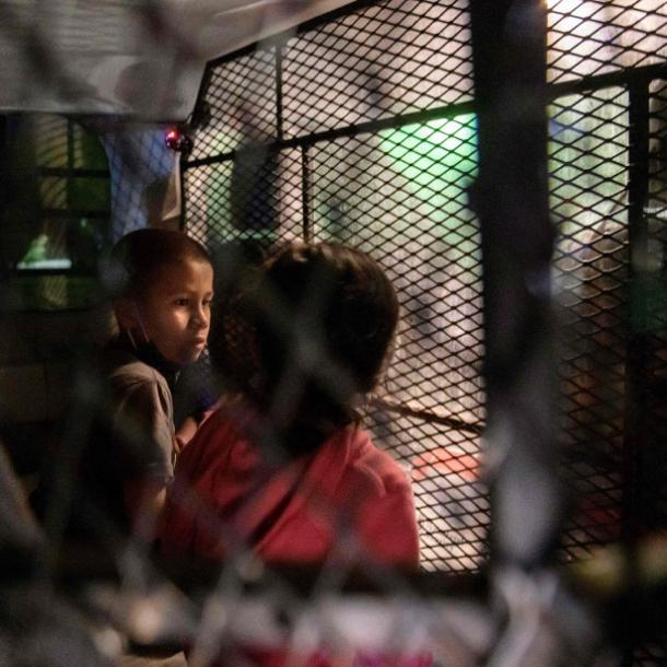 Two unaccompanied migrant children at a processing checkpoint in Roma, Texas