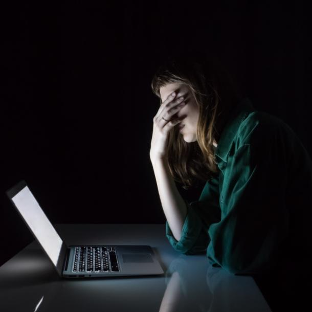 sad woman sitting in dark on the computer