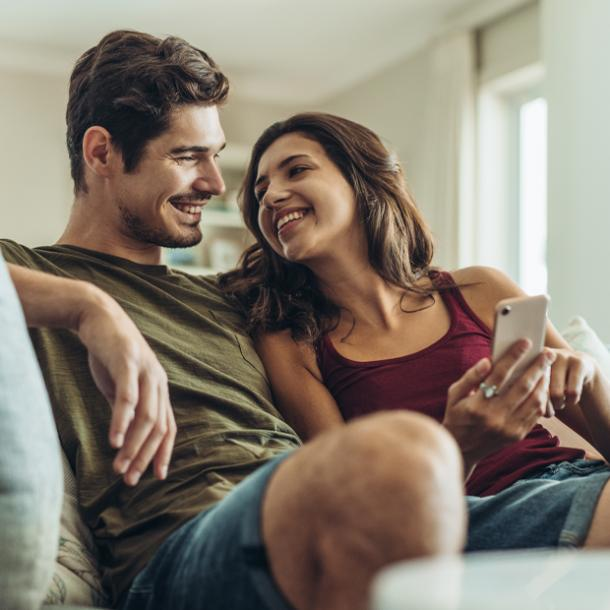 signs your ex is pretending to be over you man and woman smiling on couch