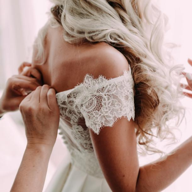 woman getting the back of her wedding dress buttoned