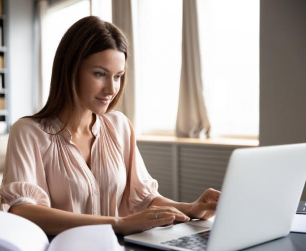 woman sitting in front of computer typing and smiling