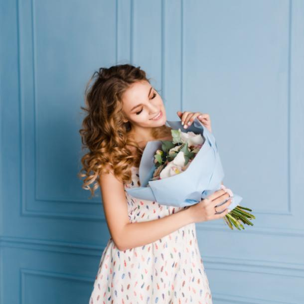 pretty woman smiling holding bouquet of flowers