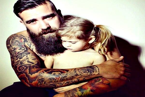 Man with beard, and tattoos with daughter in his arms.