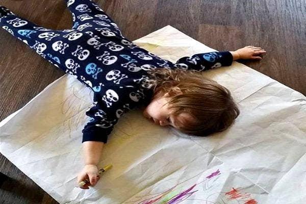 Kid asleep on his drawing.