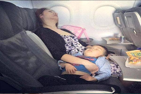 Mom and child asleep on plane.
