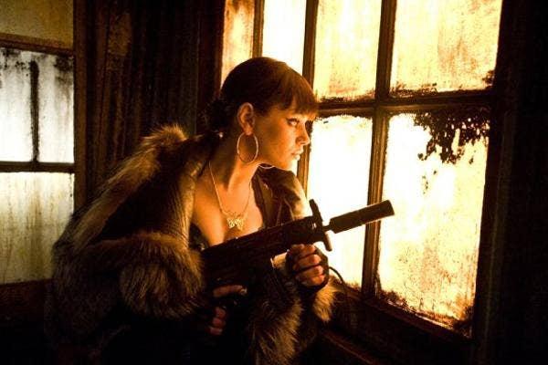 Mila Kunis with a gun