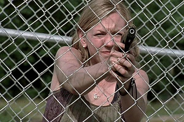 Emily Kinney as Beth Greene on AMC 'The Walking Dead' holding a gun by a fence outside the prison