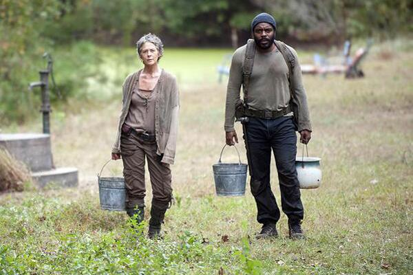 Melissa McBride as Carol Pelletier and Chad L. Coleman as Tyreese on AMC 'The Walking Dead' AMC holding buckets in the forest