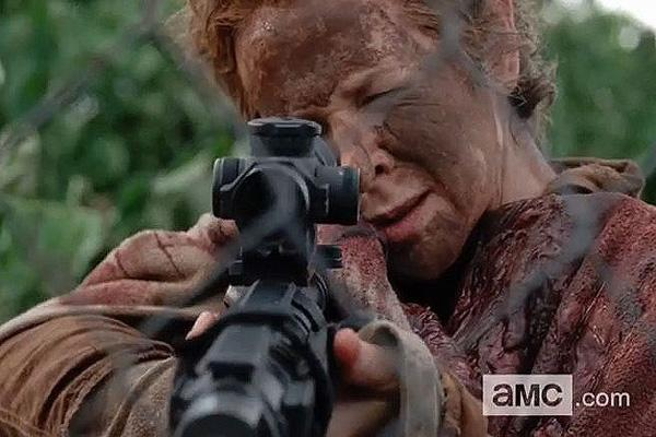 Melissa McBride as Carol Pelletier on The Walking Dead AMC shooting a machine gun