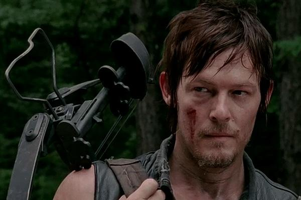 Norman Reedus as Daryl Dixon on The Walking Dead holding a crossbow AMC