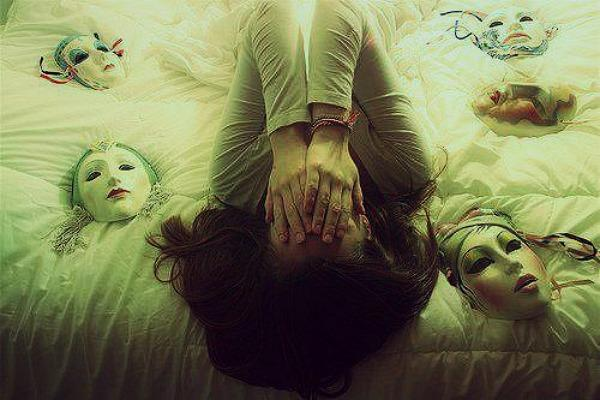 woman hides face on bed of masks