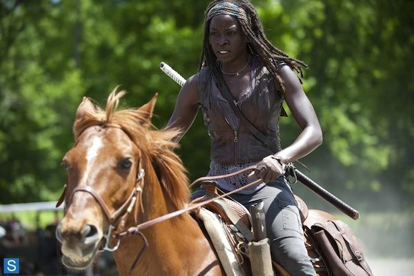 Danai Gurira as Michonne from The Walking Dead AMC riding a horse with her sword / katana