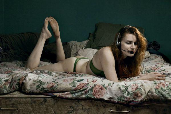 Phone sex operator on a bed.