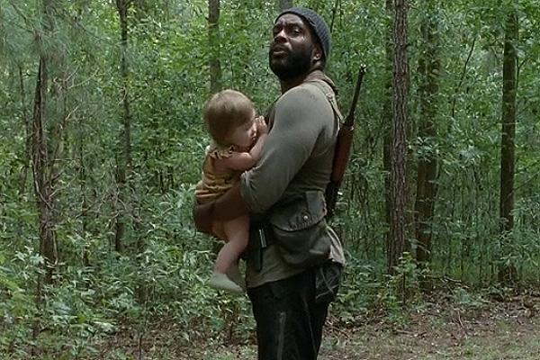 Chad L. Coleman as Tyreese on AMC 'The Walking Dead' holding baby Judith in the forest