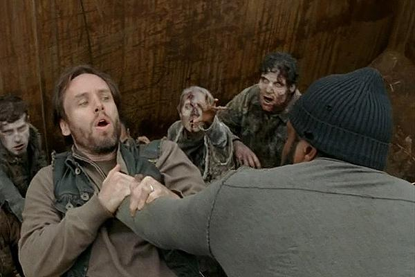 Chad L. Coleman as Tyreese on AMC 'The Walking Dead' holding a villain over a pit of walkers in the prison at Woodbury