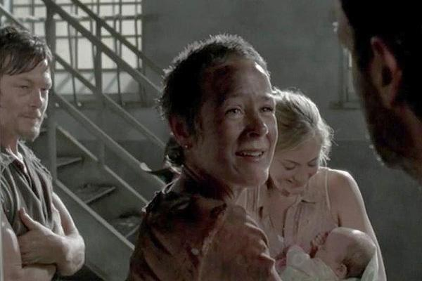 Melissa McBride as Carol Pelletier holding Judith in the prison on The Walking Dead AMC