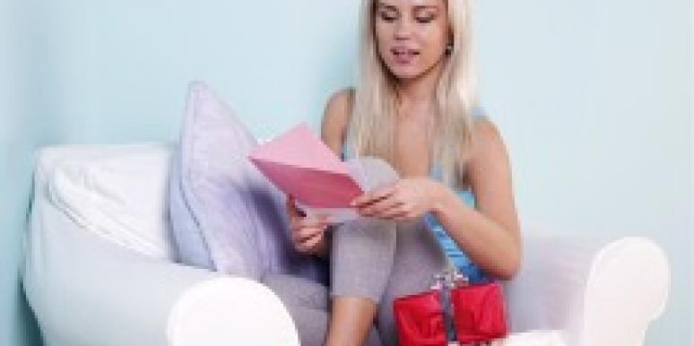 Blonde woman reading card to accompany gift