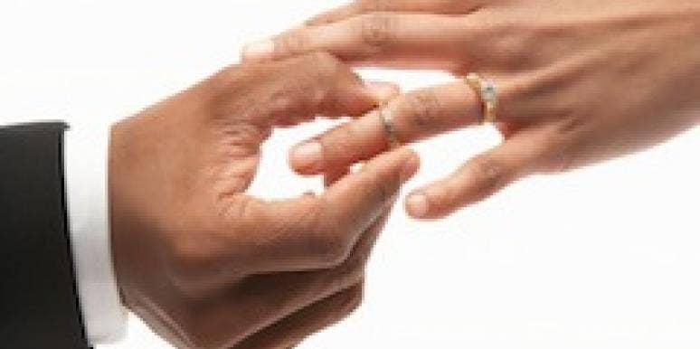 man putting wedding ring on woman