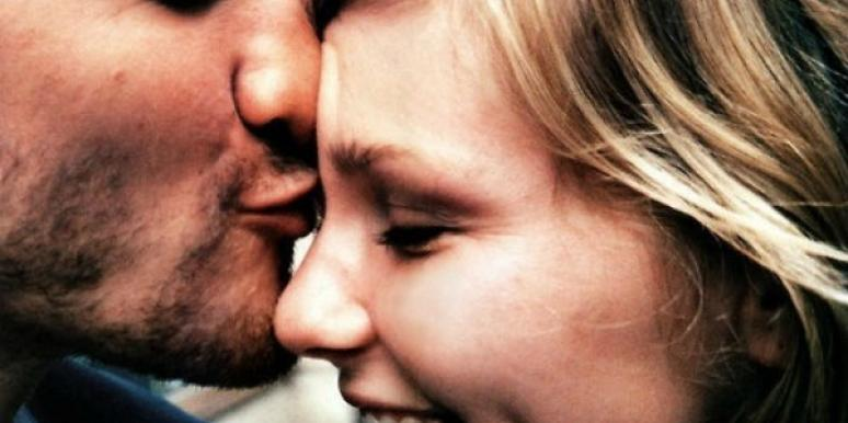 Man kissing a woman on her forehead.