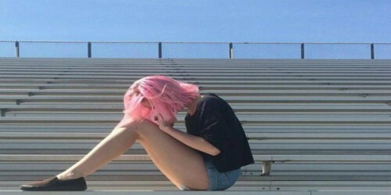 Pink haired woman sitting on bleachers.