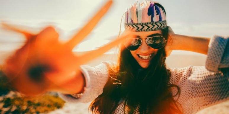 girl smiling and making a peace sign with her fingers