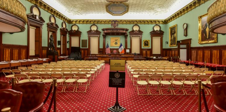 empty room where the NYC city council usually meets, filled with empty chairs and empty dais