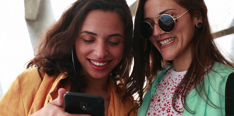 two women smiling looking at a phone