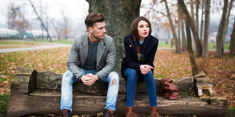 woman and man sitting on a bench angry at each other