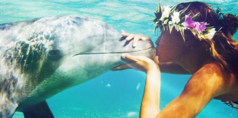 Woman kissing dolphin