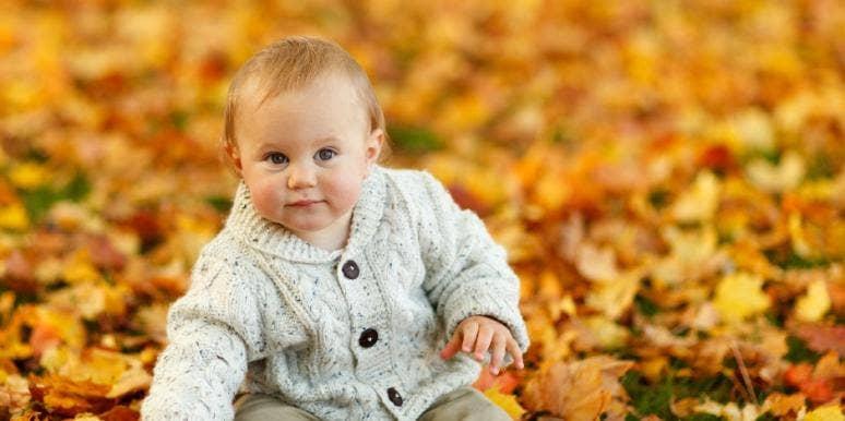 Baby boy sitting in leaves