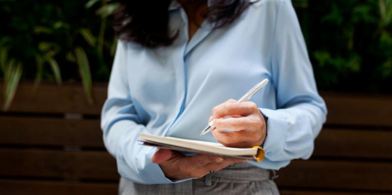 woman in business attire writing in a notebook
