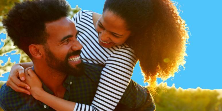 attractive Black couple snuggles playfully in front of a vibrant blue background