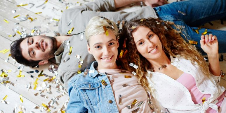 two women and one man lying on the floor with confetti