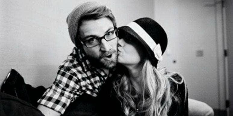 woman kissing man with beard