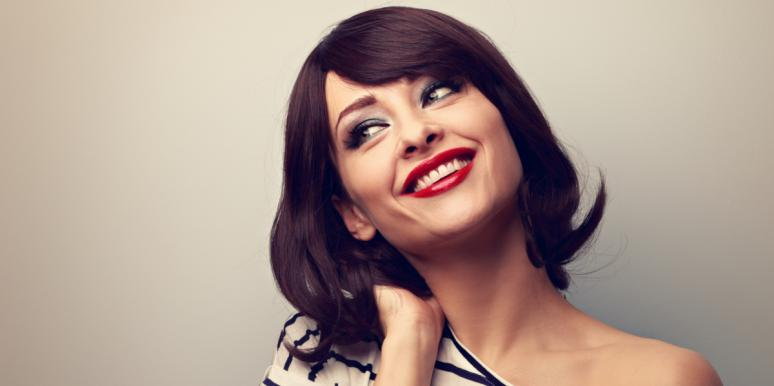 woman flipping her hair smiling with red lipstick